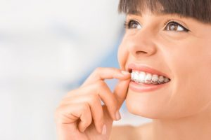 The woman uses clear aligners to straighten her teeth.