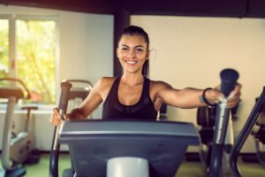 The woman uses a stair climber machine to exercise.